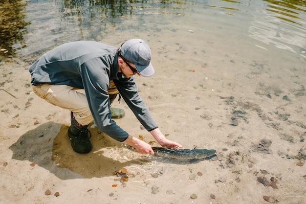 De visser laat een grote vis onder water los, een grote snoek in de vijver. goede vangst. trofee vis. visser.