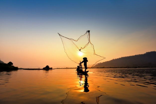 De visser van azië het netto gebruiken op houten boot werpende netto zonsondergang of zonsopgang in de mekong rivier