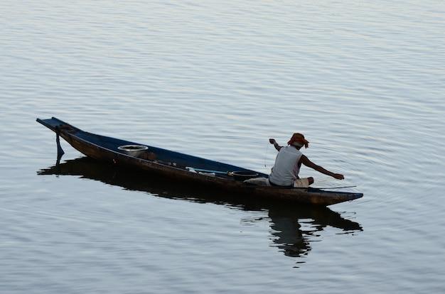 De visser zit op zijn boot in de rivier