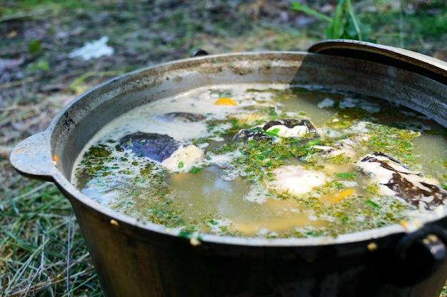 De vissoep kookt in ketel op de brandstapel van de aard. soep in een pot in het vuur. detailopname.
