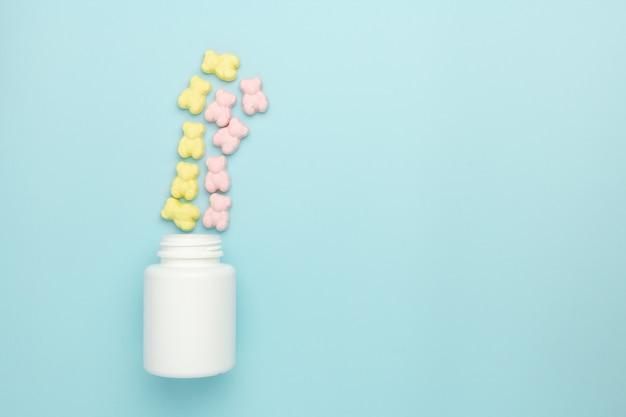 De vitaminegummies van de geleiteddybeer van de fles op een blauwe achtergrond worden bestrooid die. advertentieconcept geneeskunde voor kinderen