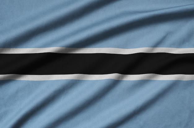 De vlag van botswana is afgebeeld op een sportdoek met veel plooien.