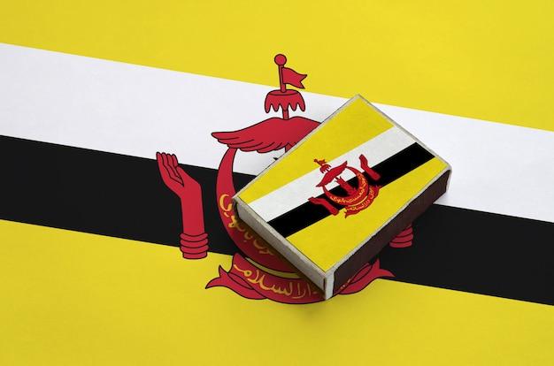 De vlag van brunei darussalam staat afgebeeld op een luciferdoosje dat op een grote vlag ligt