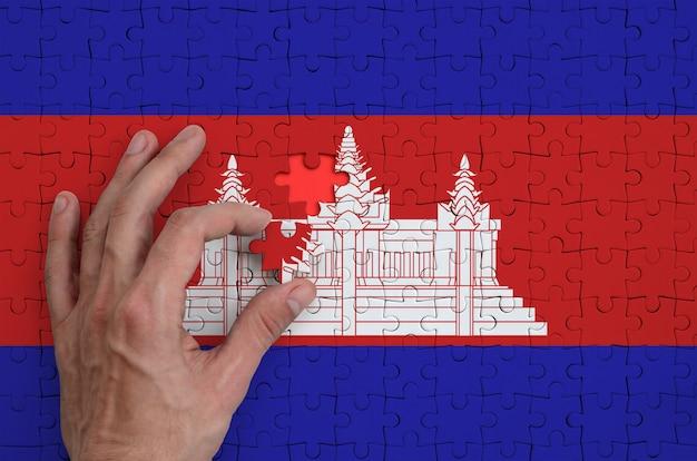 De vlag van cambodja is afgebeeld op een puzzel, die de hand van de man voltooit om te vouwen