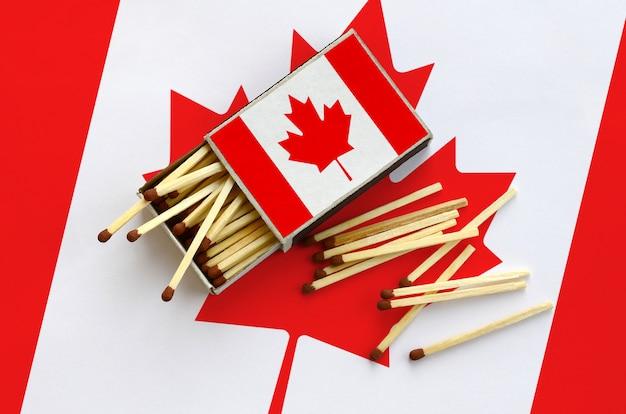 De vlag van canada wordt getoond op een open luciferdoosje, waaruit verschillende wedstrijden vallen en op een grote vlag liggen