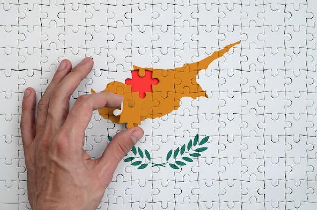 De vlag van cyprus is afgebeeld op een puzzel, die de hand van de man voltooit om te vouwen