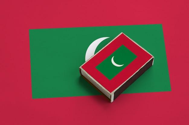 De vlag van de malediven staat afgebeeld op een luciferdoosje dat op een grote vlag ligt