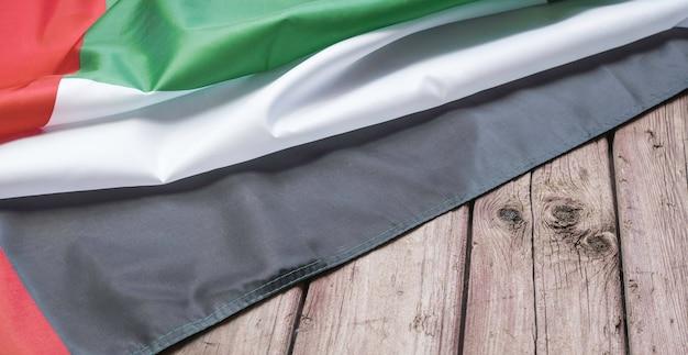 De vlag van de verenigde arabische emiraten ligt op een bruine houten achtergrond met ruimte voor tekst of afbeelding