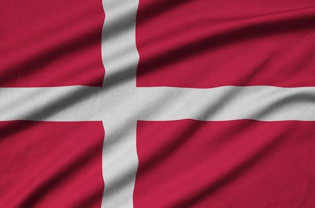De vlag van denemarken is afgebeeld op een sportdoek met veel plooien.