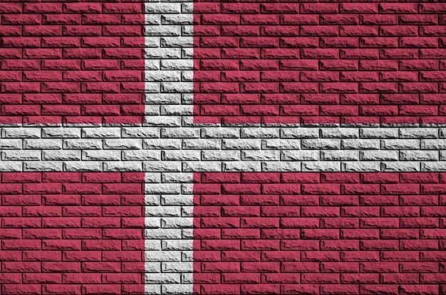 De vlag van denemarken is geschilderd op een oude bakstenen muur
