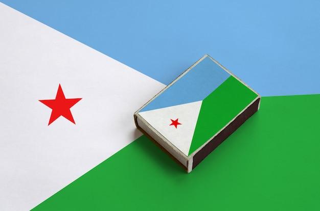 De vlag van djibouti staat afgebeeld op een luciferdoosje dat op een grote vlag ligt