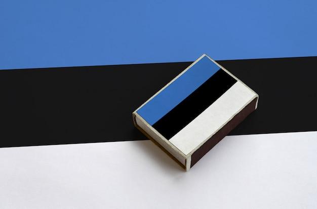 De vlag van estland staat afgebeeld op een luciferdoosje dat op een grote vlag ligt