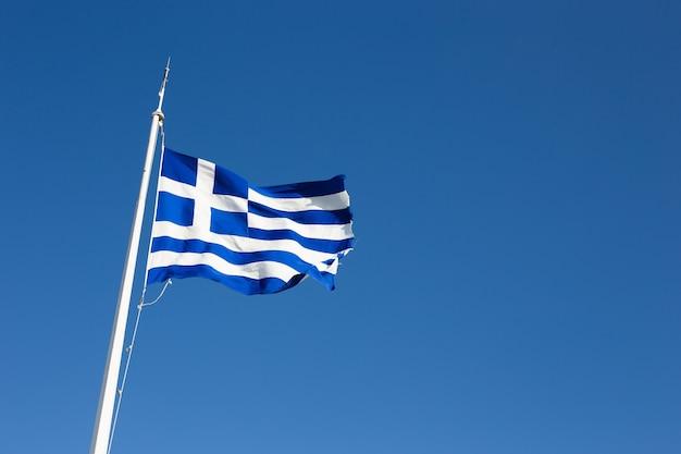 De vlag van griekenland vliegt tegen de hemel
