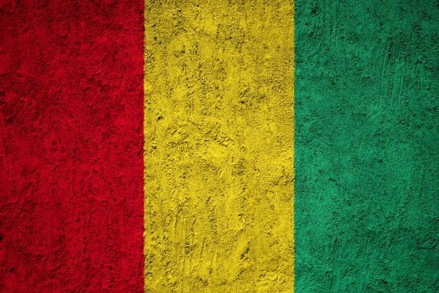 De vlag van guinea op grungemuur die wordt geschilderd