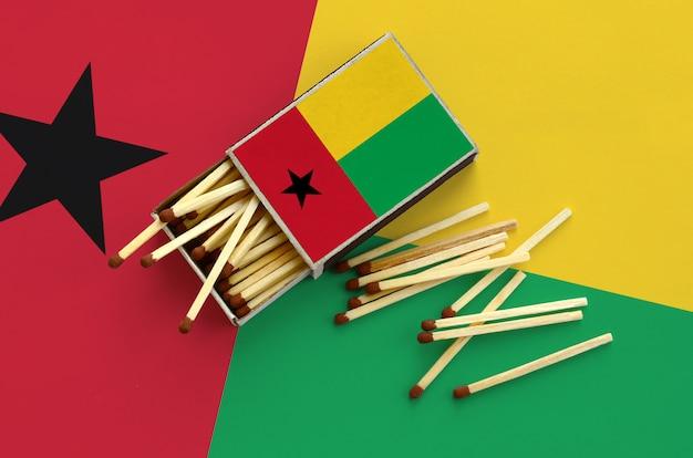 De vlag van guinee-bissau wordt weergegeven op een open luciferdoosje, waaruit verschillende wedstrijden vallen en op een grote vlag liggen