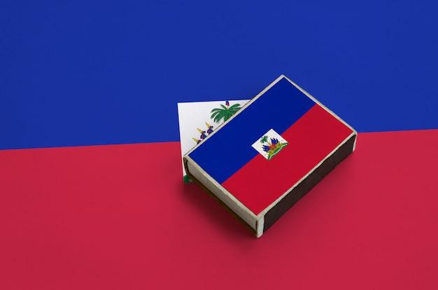 De vlag van haïti staat afgebeeld op een luciferdoosje dat op een grote vlag ligt
