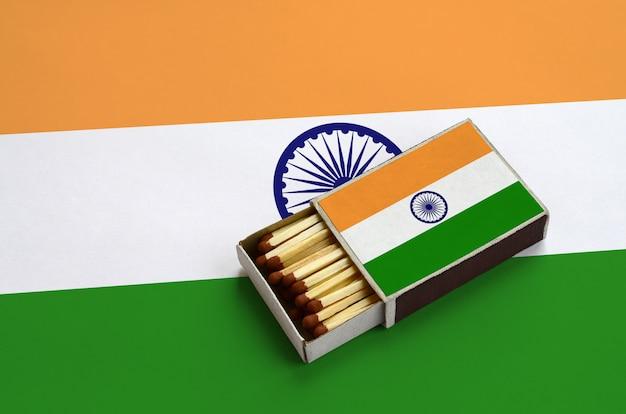 De vlag van india wordt getoond in een open luciferdoosje, dat gevuld is met lucifers en op een grote vlag ligt