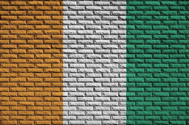 De vlag van ivoorkust is op een oude bakstenen muur geschilderd