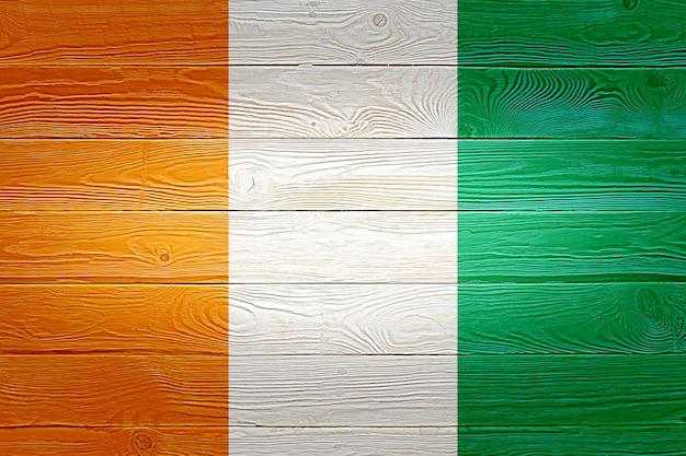 De vlag van ivoorkust op oude houten plankachtergrond die wordt geschilderd