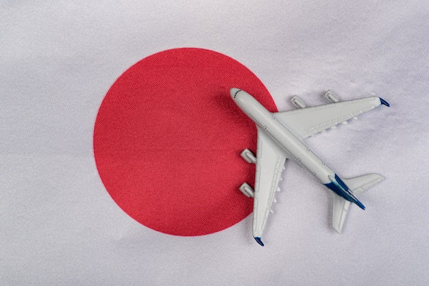 De vlag van japan en stuk speelgoed vliegtuig dichte omhooggaand. concept van vliegreizen naar japan. na quarantaine naar japan reizen.