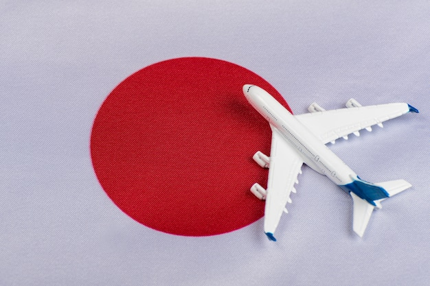 De vlag van japan en stuk speelgoed vliegtuig dichte omhooggaand