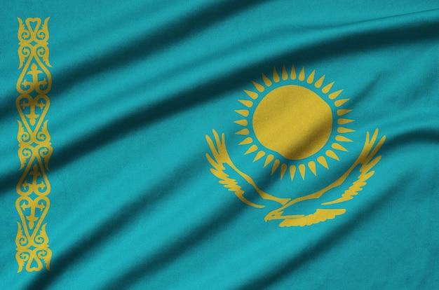 De vlag van kazachstan is afgebeeld op een sportdoek met veel plooien.