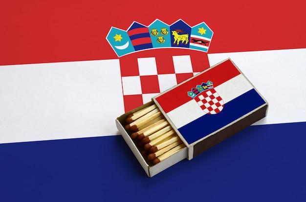 De vlag van kroatië wordt getoond in een open luciferdoosje, dat gevuld is met lucifers en op een grote vlag ligt