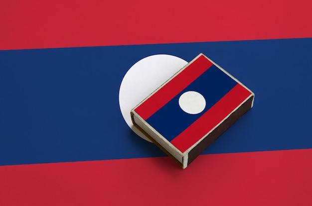 De vlag van laos staat afgebeeld op een luciferdoosje dat op een grote vlag ligt