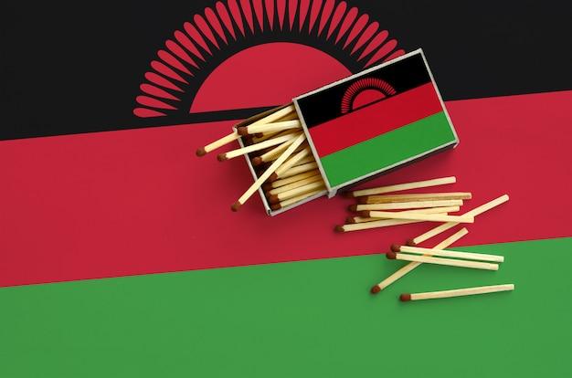 De vlag van malawi wordt getoond op een open luciferdoosje, waaruit verschillende lucifers vallen en op een grote vlag liggen