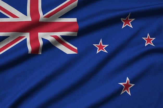 De vlag van nieuw zeeland is afgebeeld op een sportdoek met veel plooien.