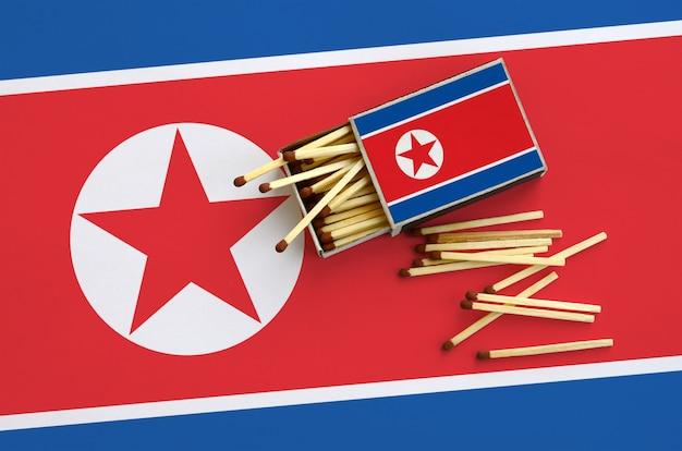 De vlag van noord-korea wordt weergegeven op een open luciferdoosje, waaruit verschillende wedstrijden vallen en op een grote vlag liggen