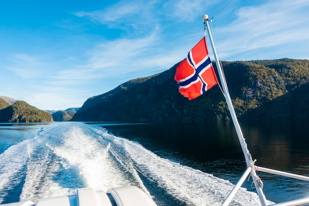 De vlag van noorwegen op veerbootcruise met blauwe hemel
