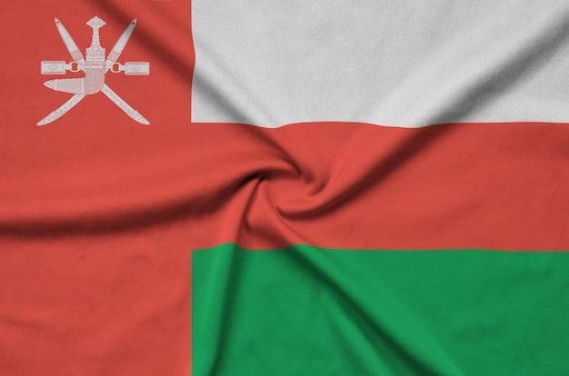 De vlag van oman is afgebeeld op een sportdoek met veel plooien.