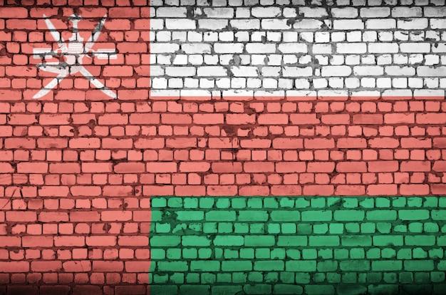 De vlag van oman is op een oude bakstenen muur geschilderd