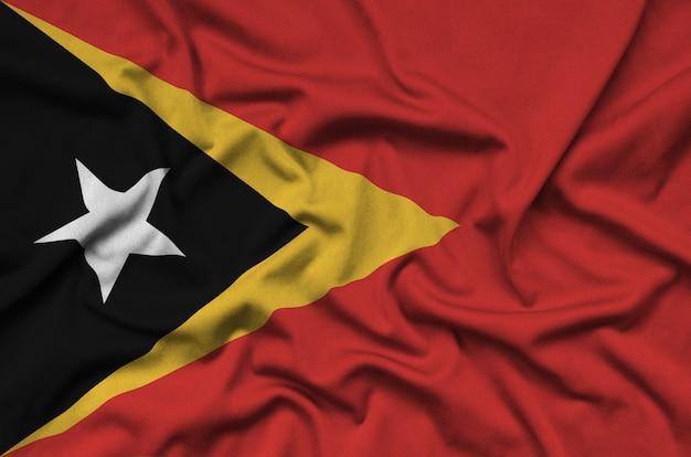 De vlag van oost-timor is afgebeeld op een sportdoek met veel plooien.