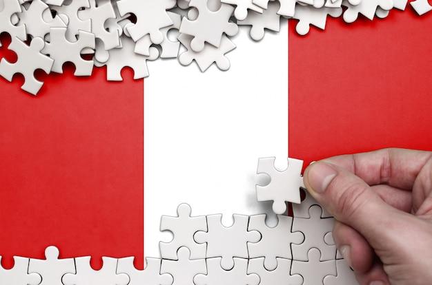 De vlag van peru is afgebeeld op een tafel waarop de menselijke hand een puzzel van witte kleur vouwt