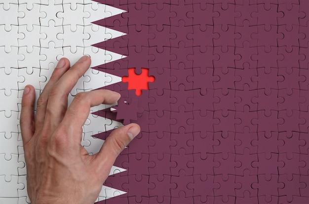 De vlag van qatar staat afgebeeld op een puzzel, die de hand van de man voltooit om te vouwen