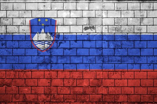 De vlag van slovenië is geschilderd op een oude bakstenen muur