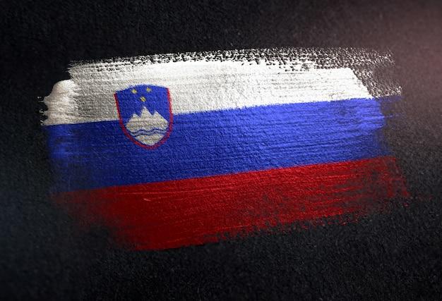 De vlag van slovenië van metaalborstelverf wordt gemaakt op grunge donkere muur die