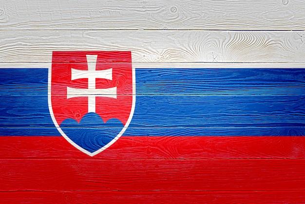 De vlag van slowakije op oude houten plankachtergrond die wordt geschilderd