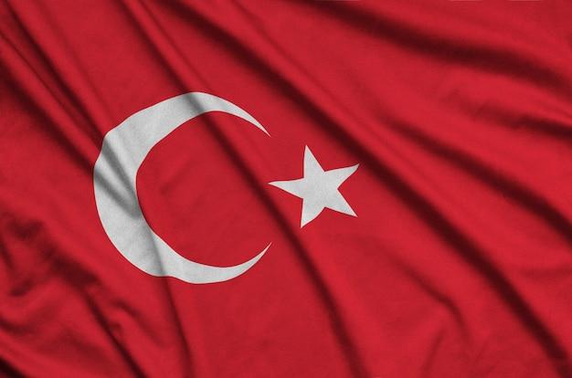 De vlag van turkije is afgebeeld op een sportdoek met veel plooien.