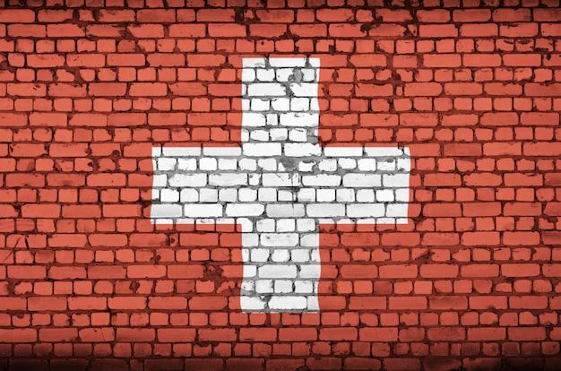 De vlag van zwitserland is op een oude bakstenen muur geschilderd