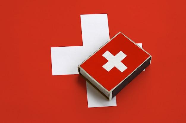 De vlag van zwitserland staat afgebeeld op een luciferdoosje dat op een grote vlag ligt