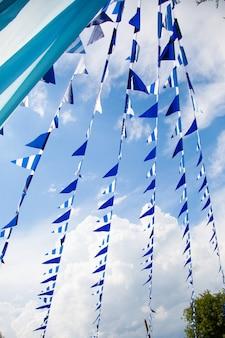 De vlaglijn van estival met blauwe binnen hemel. vlag het hangen op blauwe hemel voor de partijgebeurtenis van de pretfiesta