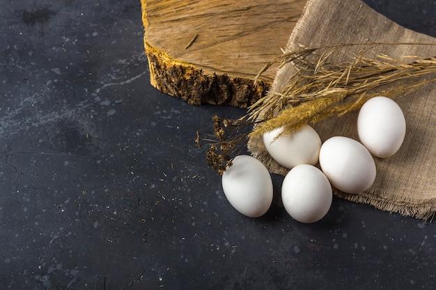 De vlakte van pasen legt rustieke samenstelling van verse witte eieren in eicel op donkere achtergrond. geen afval, milieuvriendelijk en natuurlijk materiaal. landbouw en gezond eten concept. detailopname
