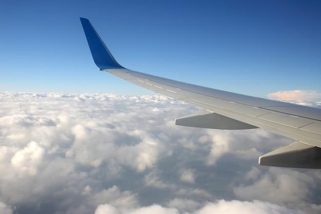 De vleugel van een vliegtuig boven de wolken