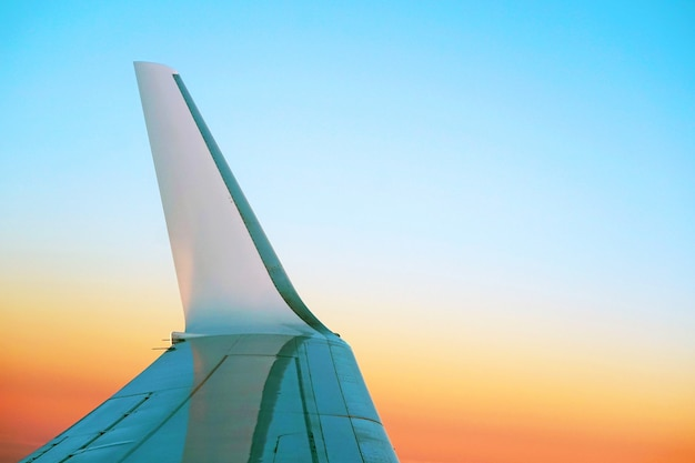 De vleugel van een vliegtuig dat in de ochtendhemel vliegt. de vleugel van het vliegtuig met de opkomst van de zon in een lichtbrander.