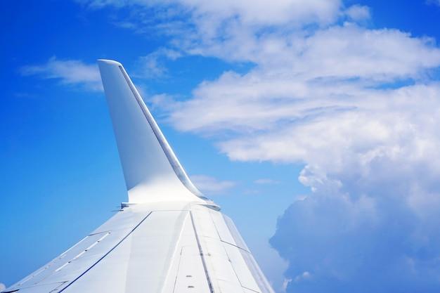 De vleugel van een vliegtuig dat in de wolken vliegt. de vleugels van het vliegtuig in de blauwe lucht en witte wolken.