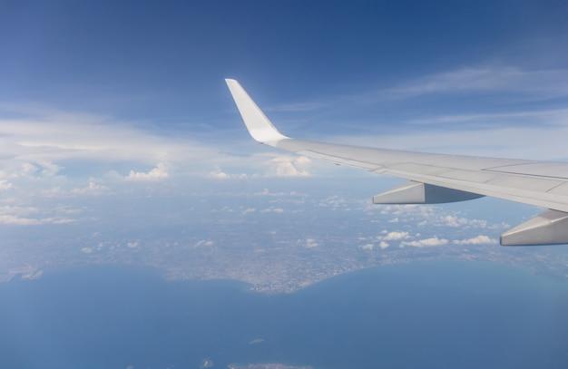 De vleugelmening van het vliegtuig uit het venster de bewolkte hemelachtergrond