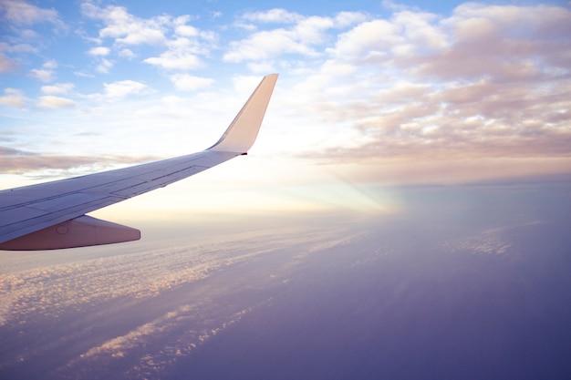 De vleugelmening van vliegtuigen van vliegtuig met mooie zonsonderganghemel en wolken